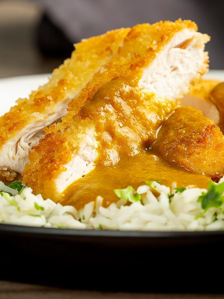 Portrait close up image of a chicken katsu curry with sliced crispy chicken breast served with coriander rice
