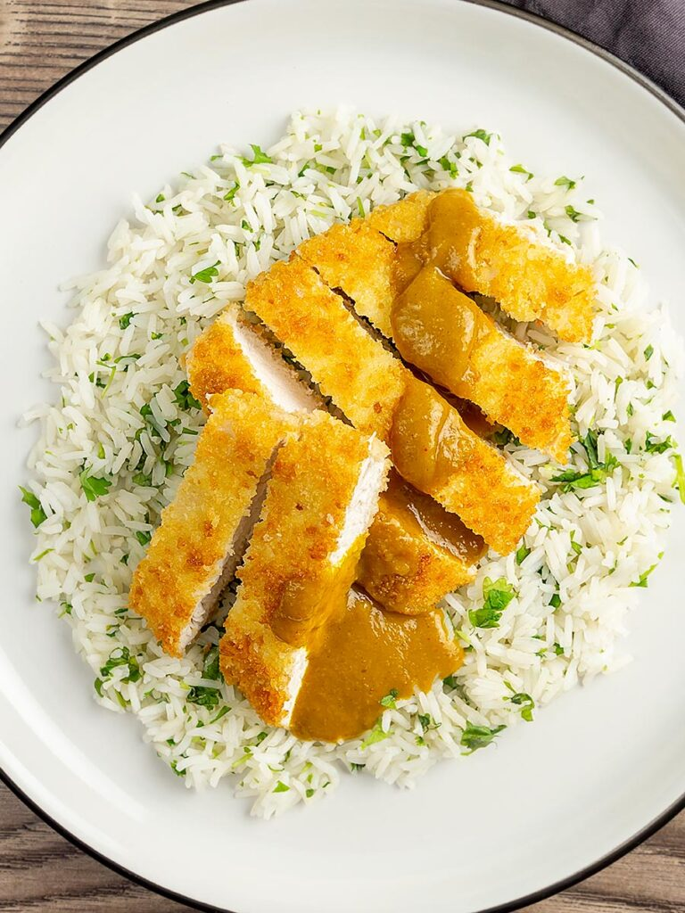 Portrait overhead image of a chicken katsu curry with sliced crispy chicken breast served with coriander rice