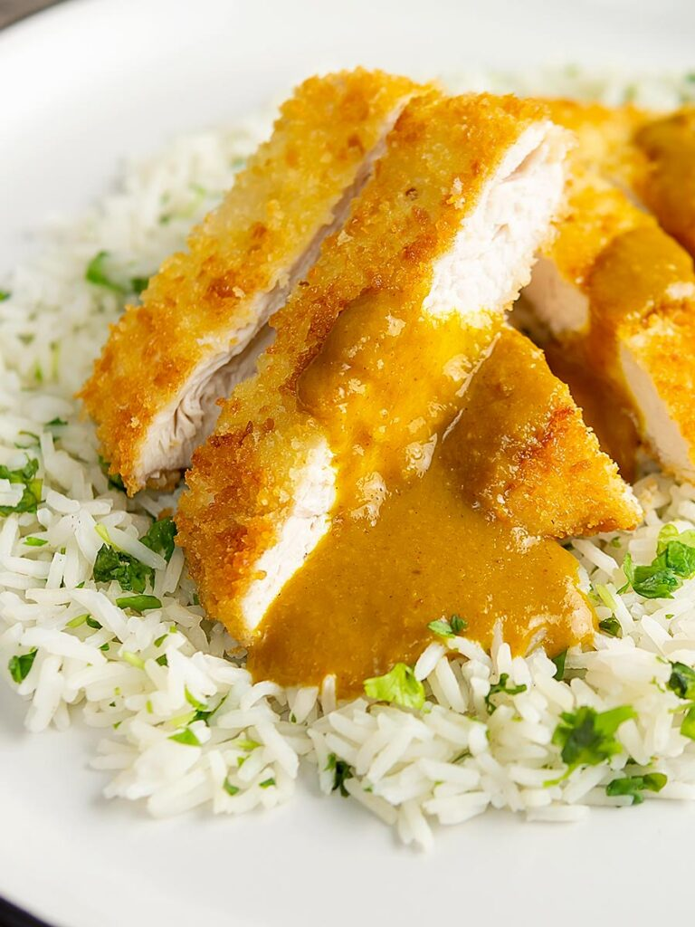 Portrait image of a chicken katsu curry with sliced crispy chicken breast served with coriander rice