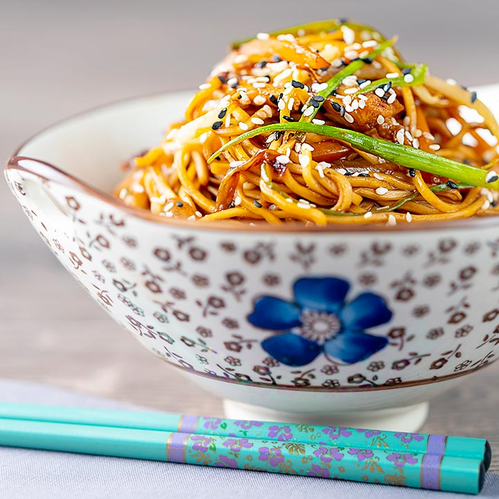 Square image of a chicken noodle stir fry, lo mein or chow mein served in a bowl with an Asian floral design