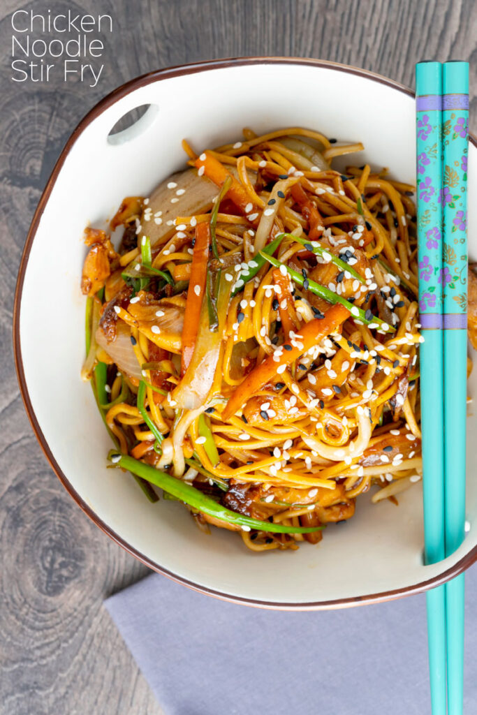 Portrait close up imag of a chicken noodle stir fry, lo mein or chow mein with turquoise chop sticks with text overlay