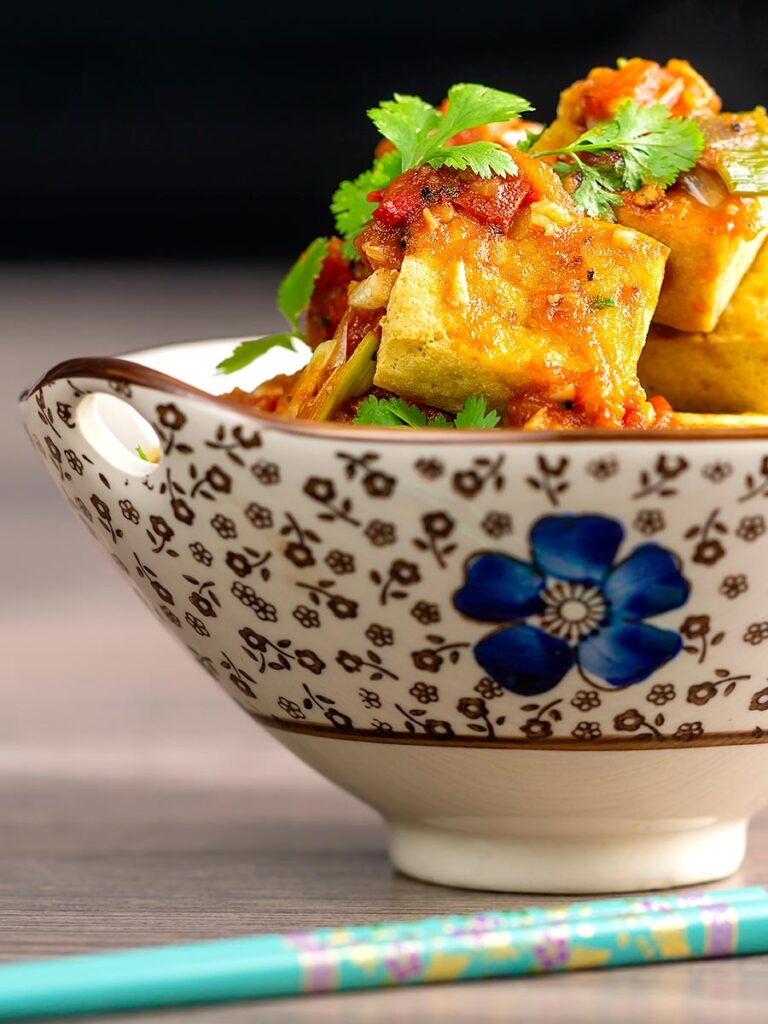Portrait image of crispy cubes fried tofu with a Vietnamese tomato sauce and coriander leaves in an bowl decorated with an Asian flower design