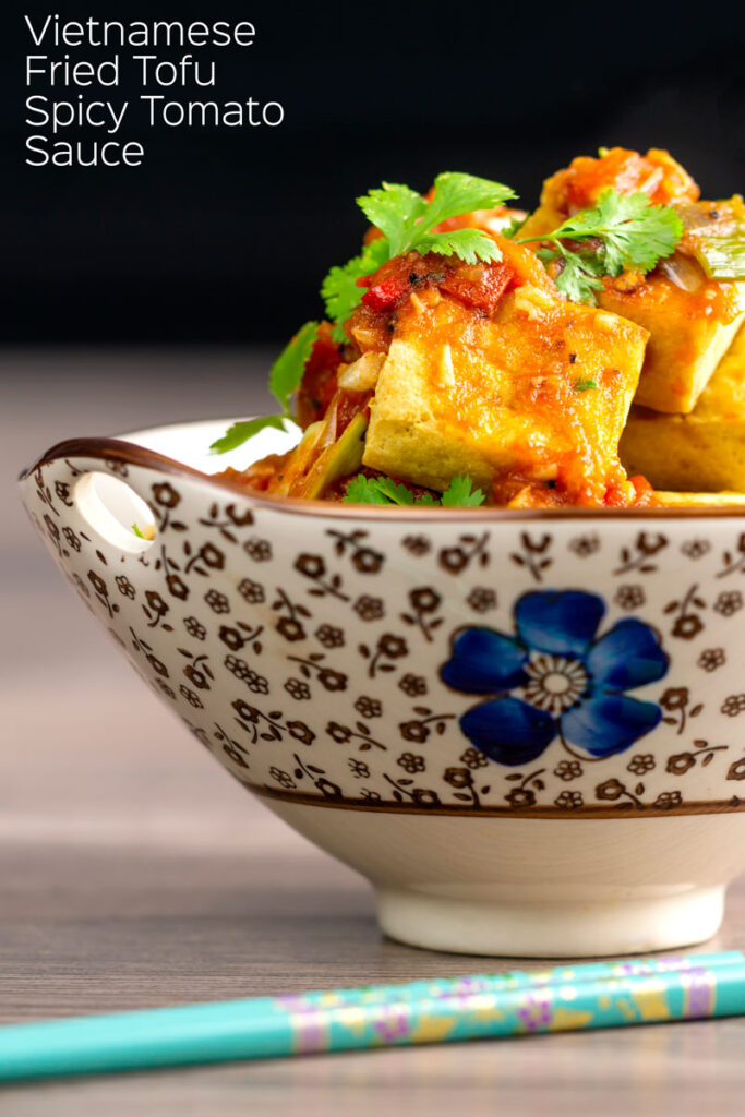 Portrait image of crispy cubes fried tofu with a Vietnamese tomato sauce and coriander leaves in an bowl decorated with an Asian flower design with text overlay