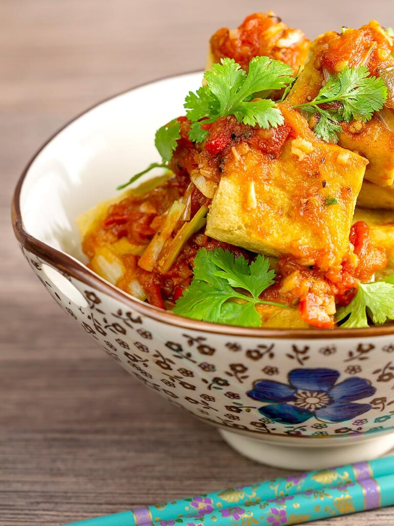 Portrait image of crispy cubes fried tofu with a Vietnamese tomato sauce and coriander leaves in an bowl