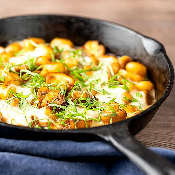 Square image of baked gnocchi with mushrooms in balsamic vinegar, mozzarella cheese and fresh basil served in a cast iron skillet