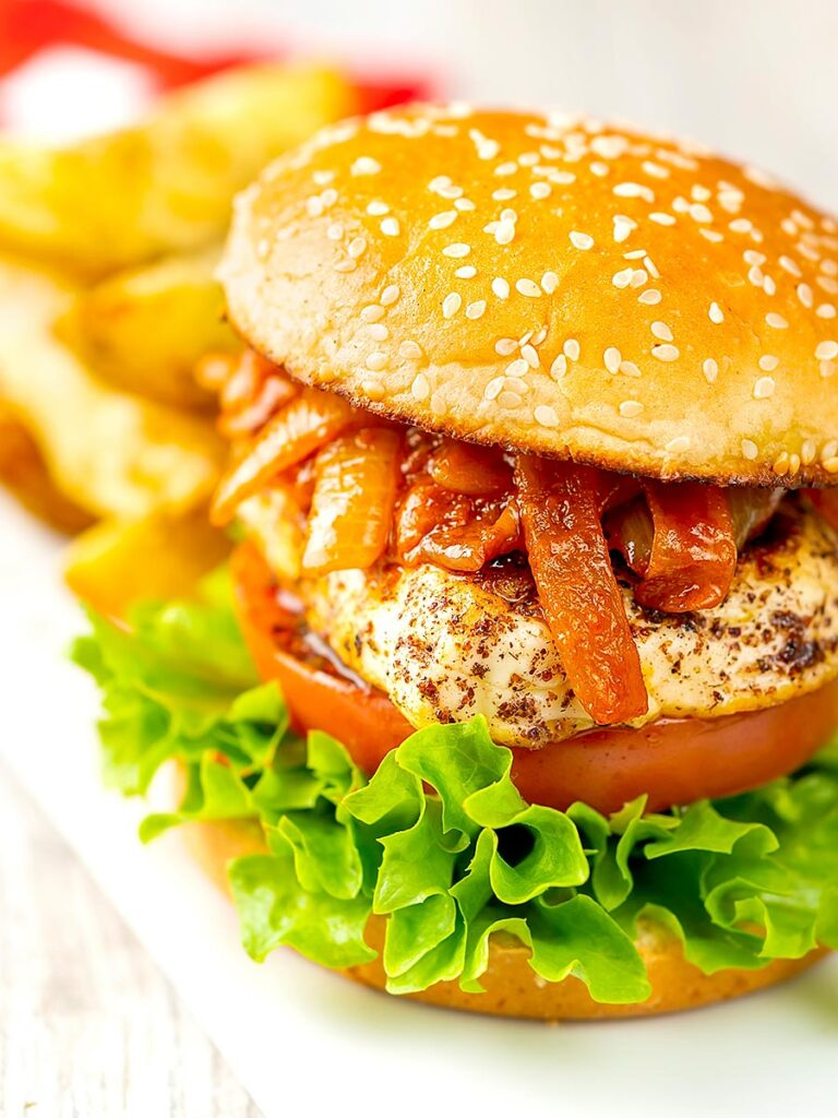 Portrait image of a halloumi burger with lettuce tomato and onions cooked in harissa served on a white platter with potato wedges