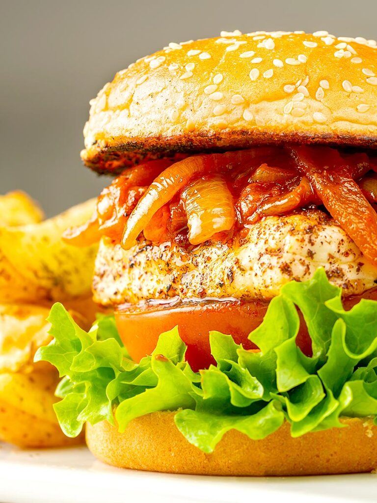 Portrait image of a halloumi burger with lettuce tomato and onions cooked in harissa