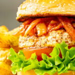Portrait image of a halloumi burger with lettuce tomato and onions cooked in harissa with text overlay
