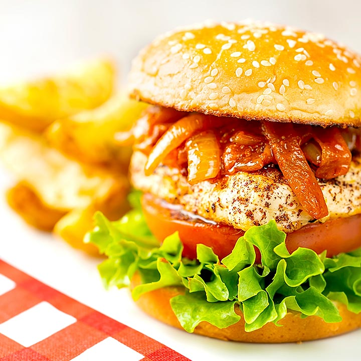 Square image of a halloumi burger with lettuce tomato and onions cooked in harissa served on a white platter with potato wedges