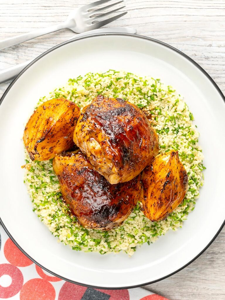 Portrait overhead image of roasted harissa chicken thighs with onion wedges served on herbed couscous