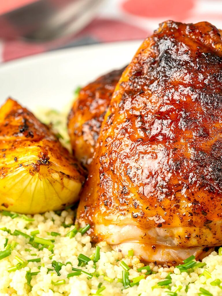 Portrait close up image of roasted harissa chicken thighs with onion wedges served on herbed couscous