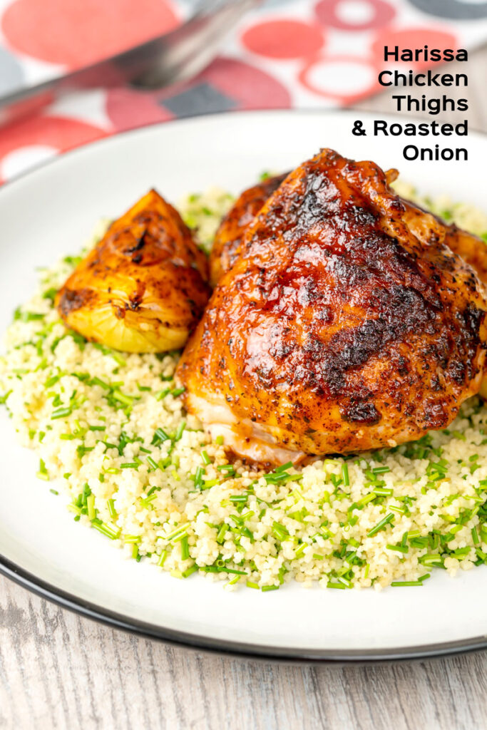 Portrait image of roasted harissa chicken thighs with onion wedges served on herbed couscous