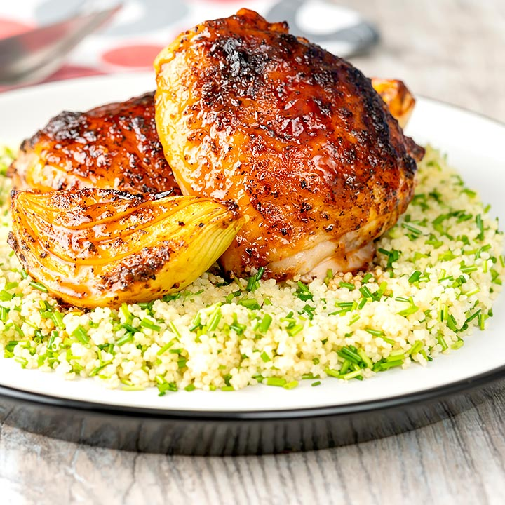 Square image of roasted harissa chicken thighs with onion wedges served on herbed couscous