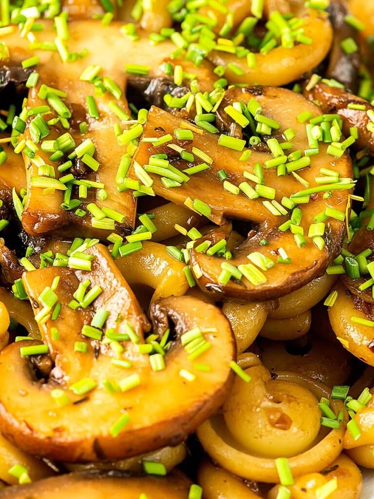 Portrait close up image of balsamic mushroom pasta served with snipped chives