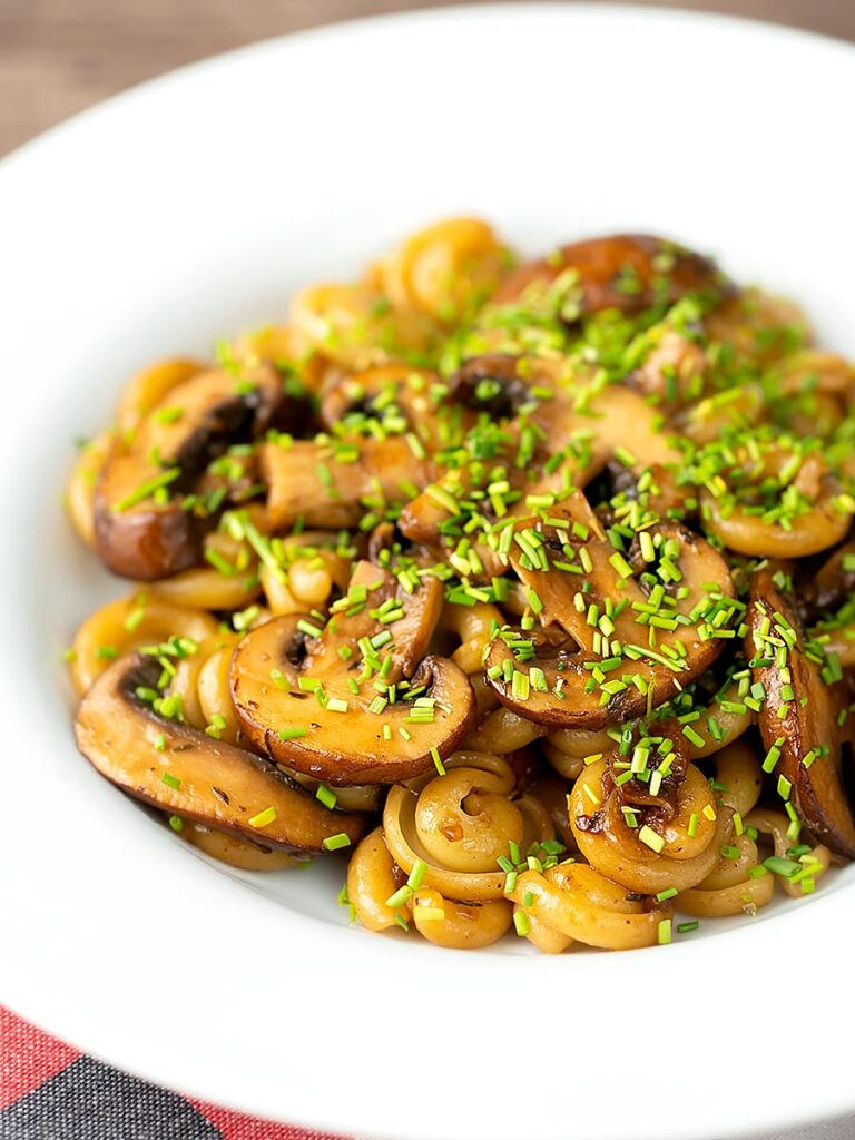 Portrait image of balsamic mushroom pasta using volanti served with snipped chives in a white bowl