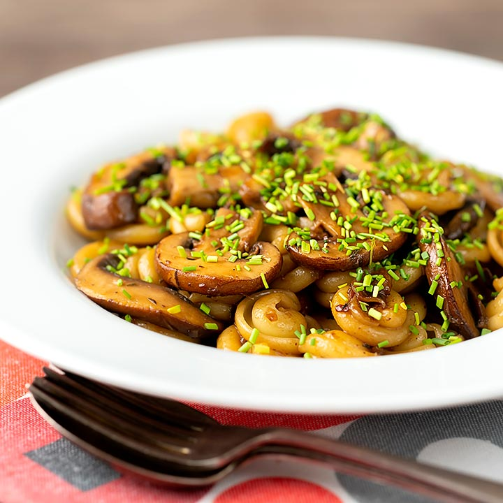Square image of balsamic mushroom pasta using volanti served with snipped chives in a white bowl
