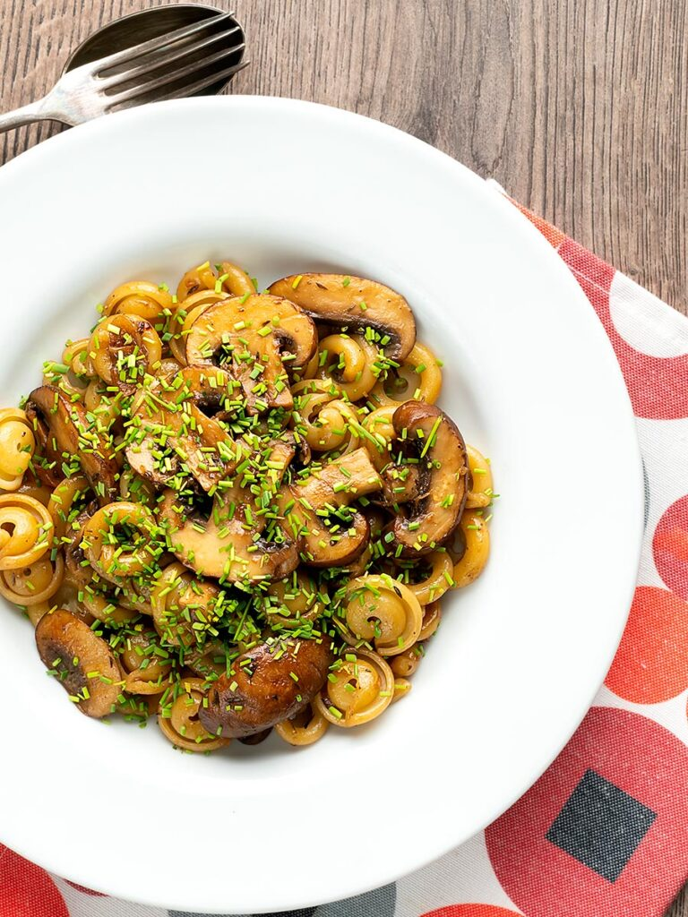 Portrait overhead image of balsamic mushroom pasta using volanti served with snipped chives in a white bowl