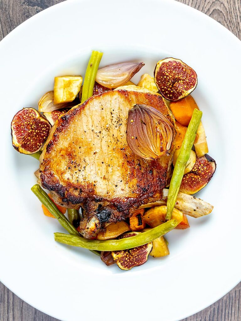 Portrait overhead image Pork chops with figs form a tray bake served in a shallow white bowl