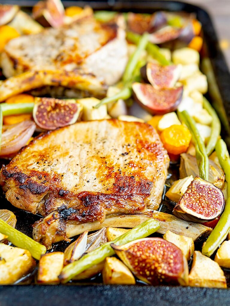 Portrait image of a pork chop tray bake with figs, green beans and roots