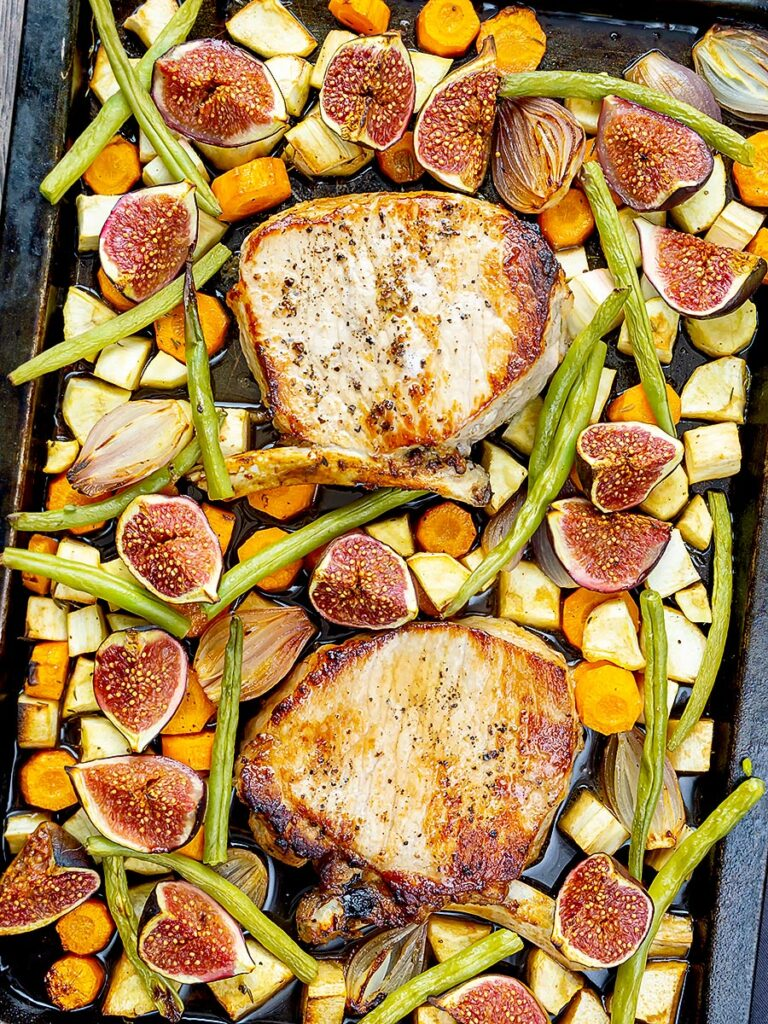 Portrait overhead of a pork chop tray bake with figs, green beans and roots
