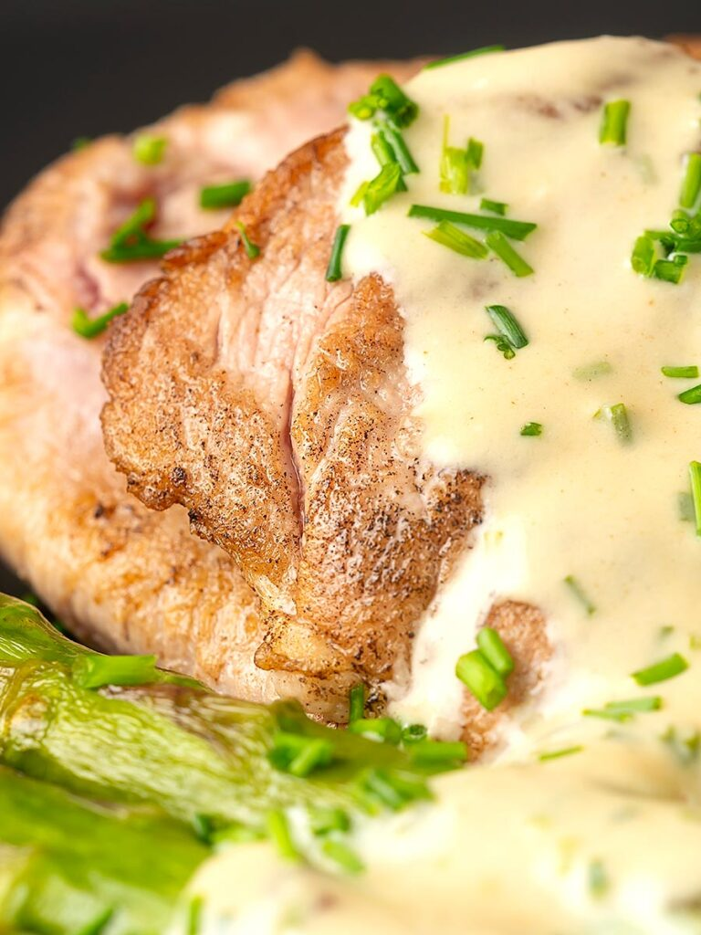 Portrait close up image of pork fillet medallions with a creamy Camembert sauce and snipped chives