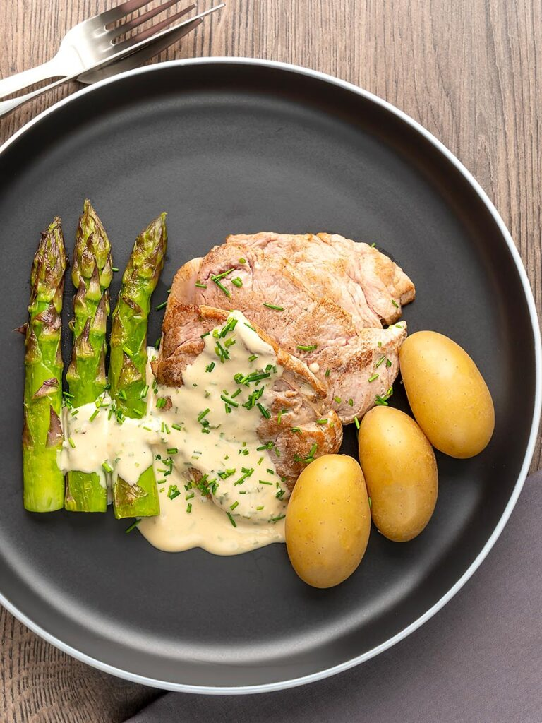 Portrait overhead image of pork fillet medallions with a creamy Camembert sauce and snipped chives asparagus and simply boiled potatoes