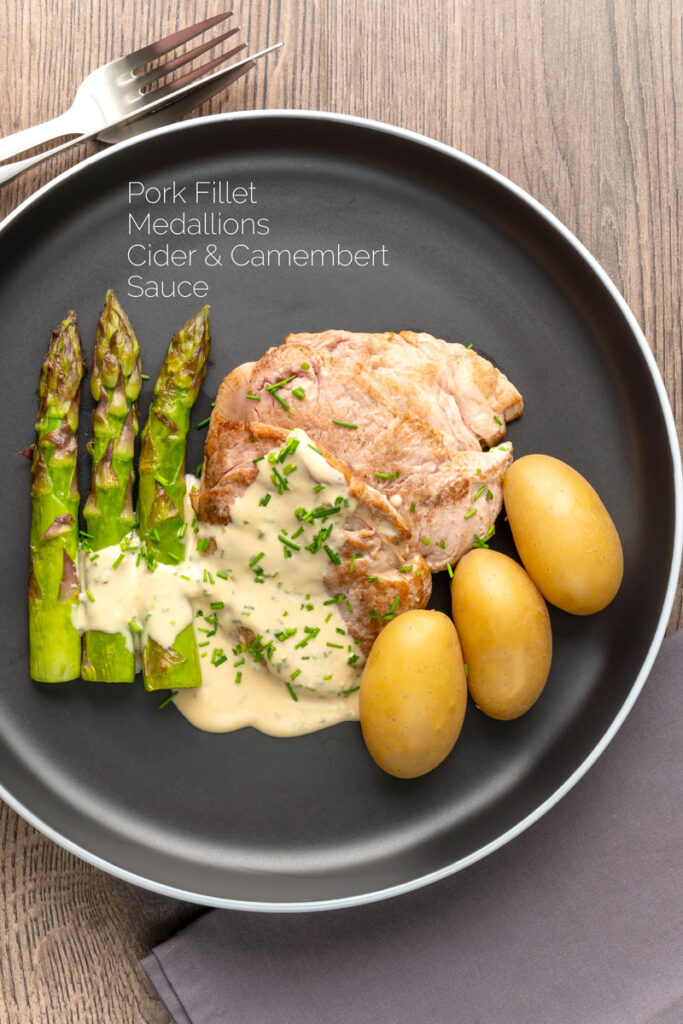Portrait overhead image of pork fillet medallions with a creamy Camembert sauce and snipped chives asparagus and simply boiled potatoes with a text overlay