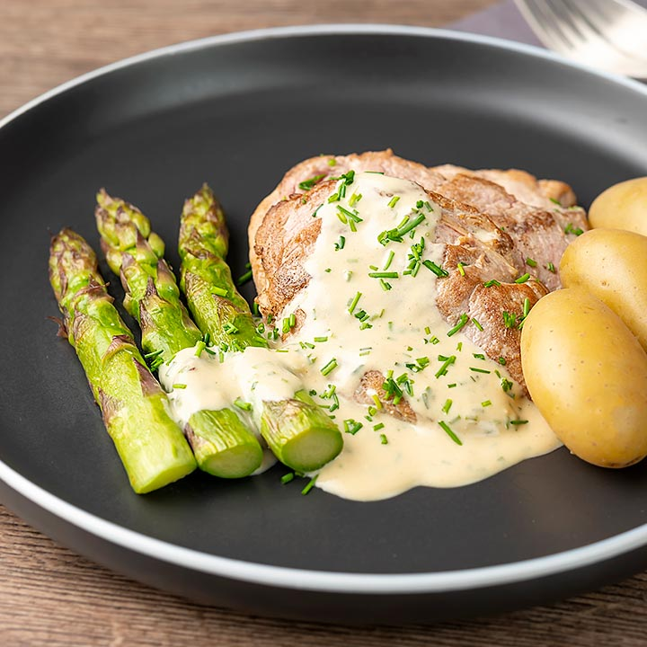 Square image of pork fillet medallions with a creamy Camembert sauce and snipped chives asparagus and simply boiled potatoes