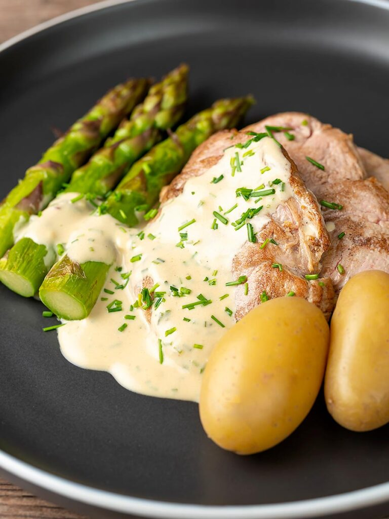 Portrait image of pork fillet medallions with a creamy Camembert sauce and snipped chives asparagus and simply boiled potatoes