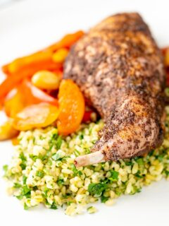 Portrait image of a rabbit leg tagine with almonds and dried apricots served with herby bulgur wheat on a white plate