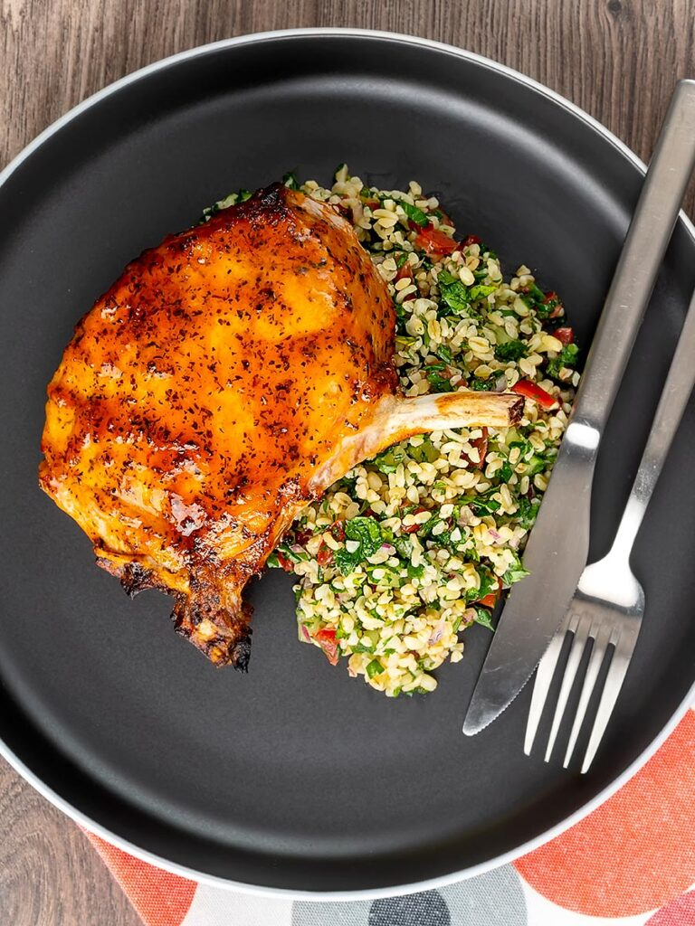 Portrait overhead image of harissa glazed roast pork chops served on a grey plate with tabbouleh salad