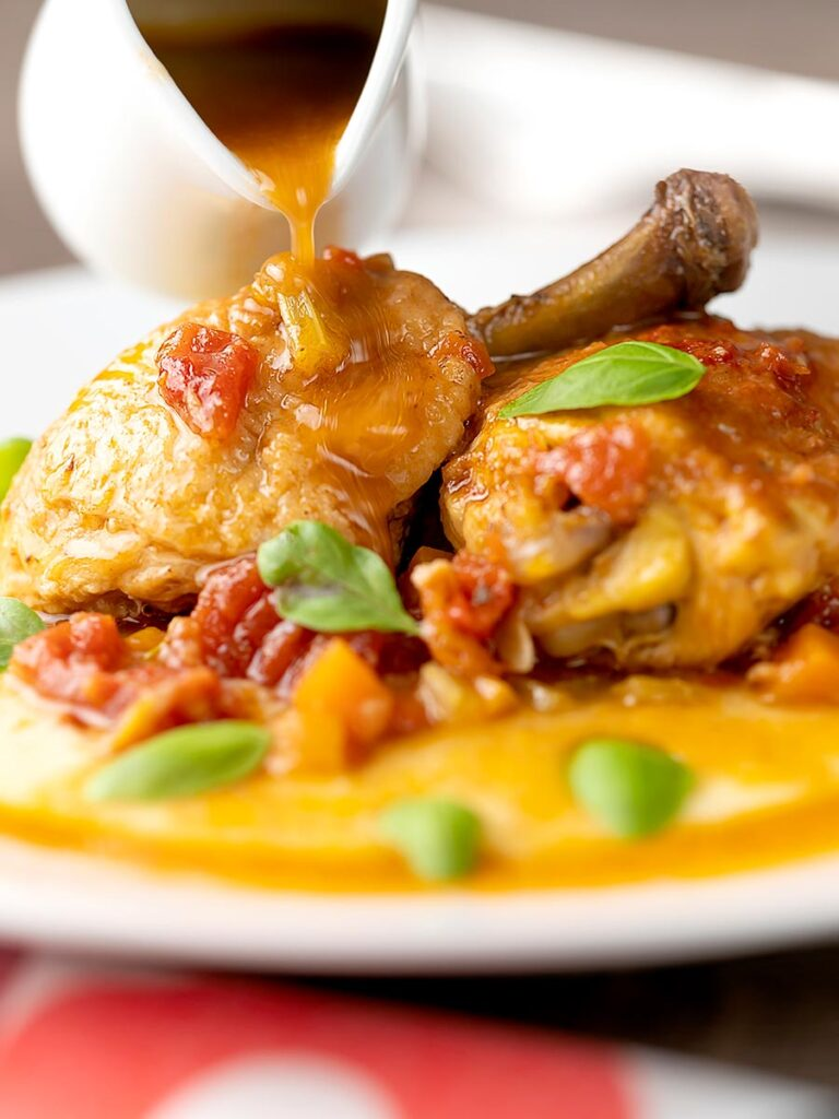 Portrait close up image of slow cooker chicken cacciatore served on a bed of polenta with extra sauce being poured from a sauce jug