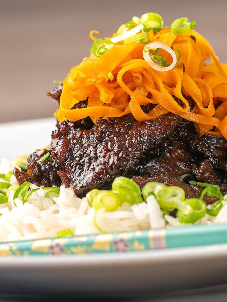 Portrait image of sticky crispy chilli beef with fried carrots on a bed of white rice