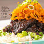 Portrait image of sticky crispy chilli beef with fried carrots on a bed of white rice with text overlay