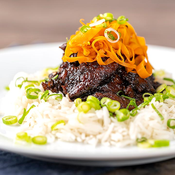 Square image of sticky crispy chilli beef with fried carrots on a bed of white rice