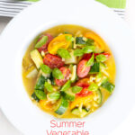 Portrait overhead image of a summer vegetable soup featuring courgettes, tomato and new potatoes served in a white shallow bowl with text overlay