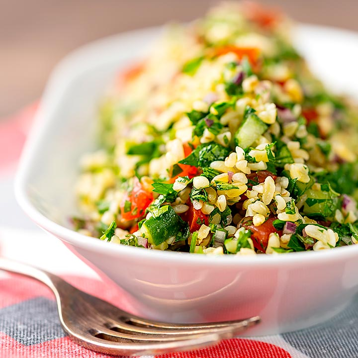 Square image of a herby tabbouleh salad served in a white bowl