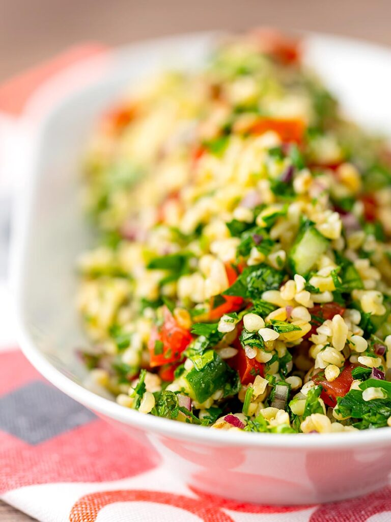 Portrait shallow depth of field image of a herby tabbouleh salad served in a white bowl