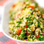 Portrait shallow depth of field image of a herby tabbouleh salad served in a white bowl with text overlay