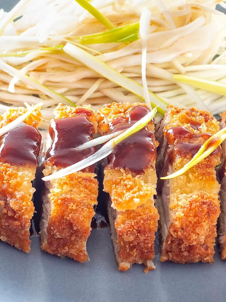 Portrait close up image of pork tonkatsu with homemade katsu sauce served with Japanese shredded cabbage