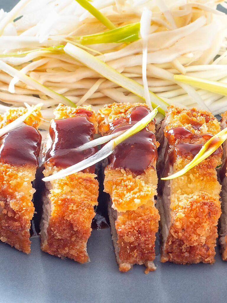 Portrait close up image of pork tonkatsu with homemade katsu sauce served with Japanese shredded cabbage