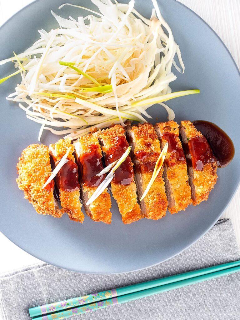 Portrait overhead image of pork tonkatsu with homemade katsu sauce served with Japanese shredded cabbage