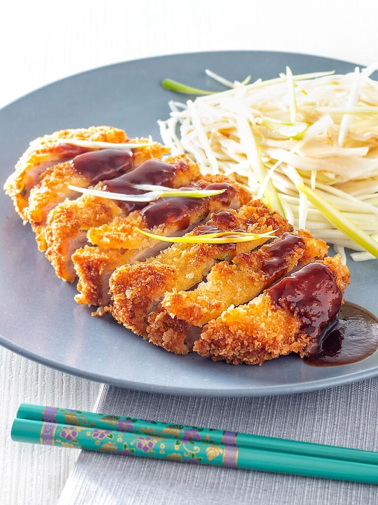 Portrait image of pork tonkatsu with homemade katsu sauce served with Japanese shredded cabbage