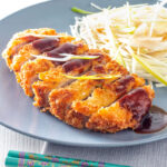 Portrait image of pork tonkatsu with homemade katsu sauce served with Japanese shredded cabbage with text overlay