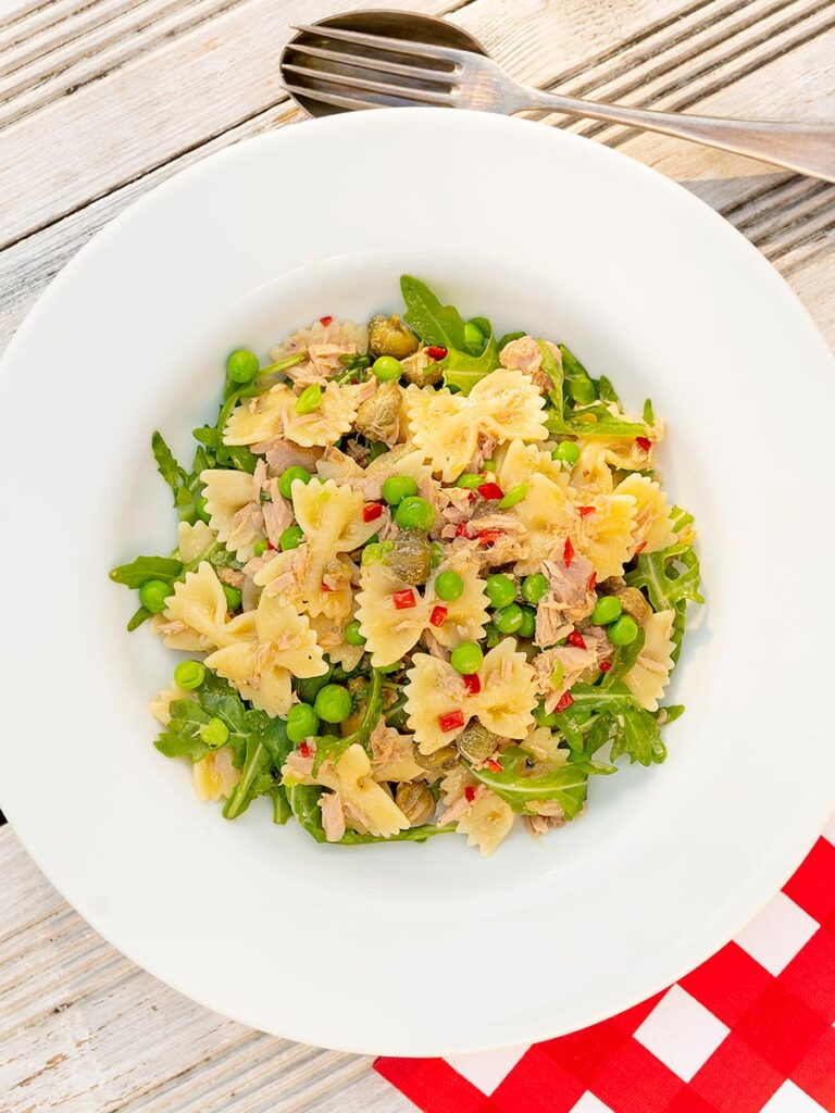Portrait overhead image of a tuna pasta salad with peas, chilli and rocket (arugula) served in a shallow white bowl