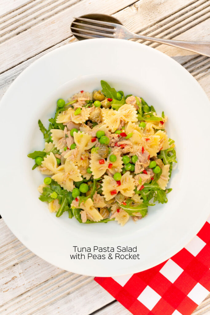 Portrait overhead image of a tuna pasta salad with peas, chilli and rocket (arugula) served in a shallow white bowl with text overlay