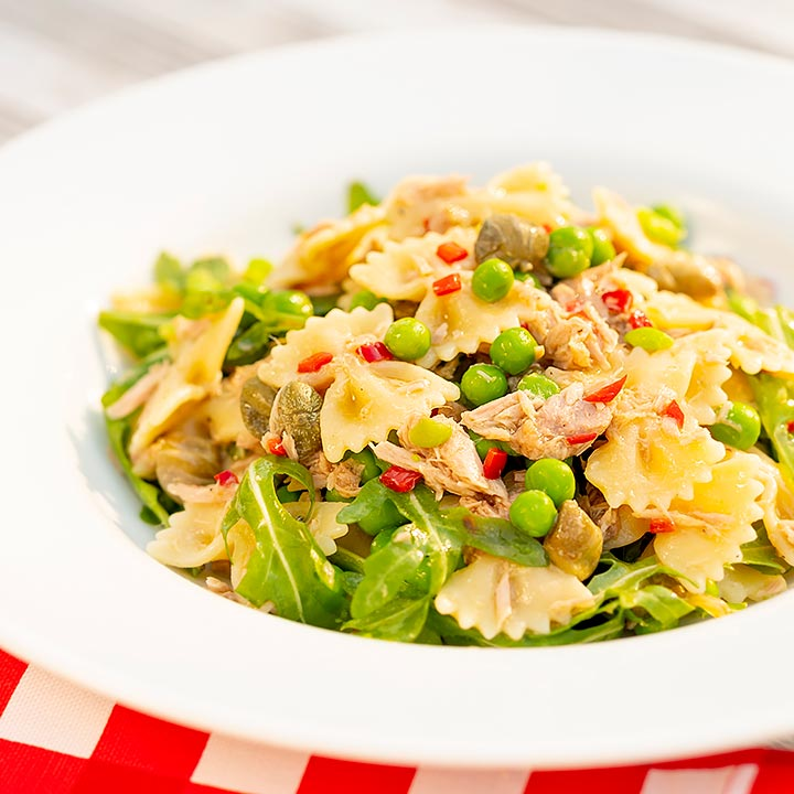 Square image of a tuna pasta salad with peas, chilli and rocket (arugula) served in a shallow white bowl
