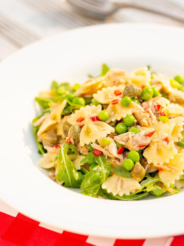 Portrait image of a tuna pasta salad with peas, chilli and rocket (arugula) served in a shallow white bowl