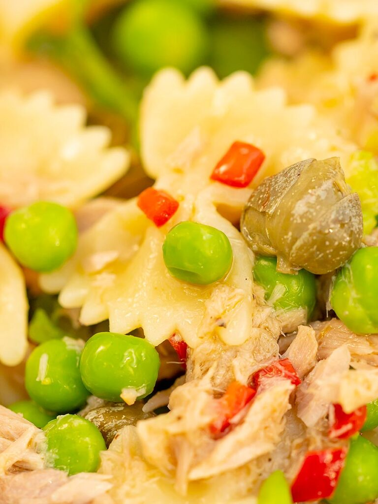 Portrait close up image of a tuna pasta salad with peas, chilli and rocket (arugula)