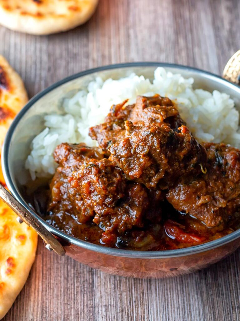 Portrait overhead image of a beef vindaloo curry in a copper coated curry bowl served with basmati rice and a naan bread